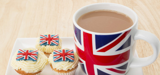 Cupcakes and a mug of hot tea with a decoration of a UK Union Jack flag - studio shot