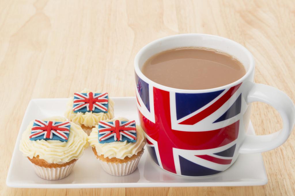 Cupcakes and a mug of hot tea with a decoration of a UK Union Jack flag - studio shot